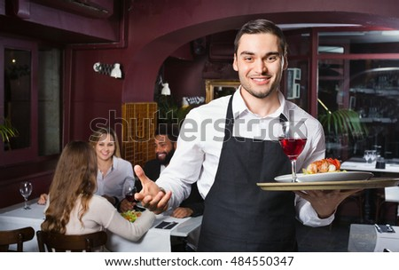 Glad young waiter taking care of adults at cafe table