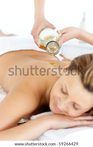 Glad young woman enjoying a back massage with oil in a spa center - stock photo