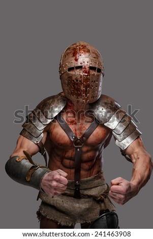 Gladiator in helmet with muscular body shows his strength