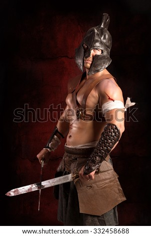 Gladiator posing isolated in a dark background