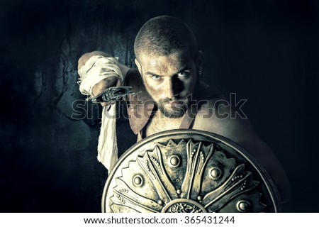 Gladiator posing with shield and sword in a dark background
