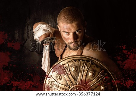 Gladiator posing with shield and sword in a dark background with blood