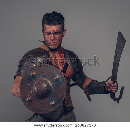 Gladiator prepares to attack his enemy holding sword and shield - stock photo