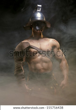 Gladiator standing in a smoke in helmet and with sword - stock photo