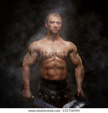 Gladiator standing in a smoke with helmet and sword  - stock photo