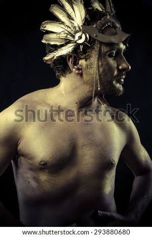 Gladiator, Warrior with helmet and sword with his body painted gold dust - stock photo