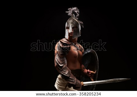 Gladiator with sword and armor on a black background - stock photo