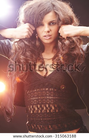 Glam rock girl in black leather jacket and lace tanktop looking at camera - stock photo