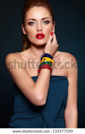 glamor closeup portrait of beautiful sexy stylish blond Caucasian young woman model with bright makeup, with red lips,  with perfect clean skin with colorful accessories in blue cloth - stock photo