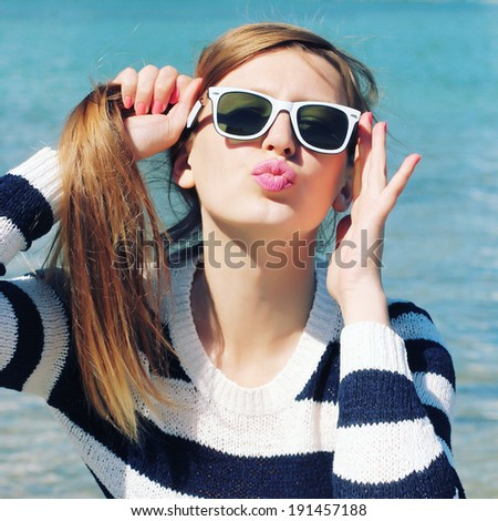 Glamor portrait of a beautiful blonde in sunglasses. Hipster girl relaxing on a sunny beach. Photo toned style instagram filters - stock photo
