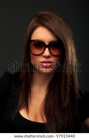 Glamor portrait of a beautiful long hair brunette woman wearing sunglasses studio shot