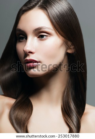 Glamor portrait of beautiful young girl in the studio on a gray background, the concept of health and beauty - stock photo