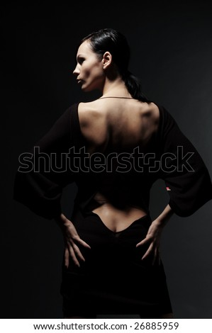 glamor woman in dress with naked back over black background - stock photo