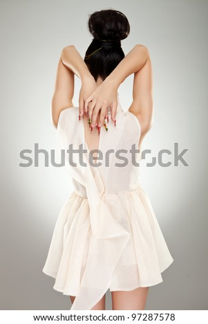 glamor woman in dress with naked back over studio  background - stock photo