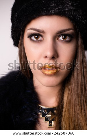 Glamorous attractive sultry young woman with a moody serious expression in elegant winter fashion and jewellery accessories looking at the camera - stock photo