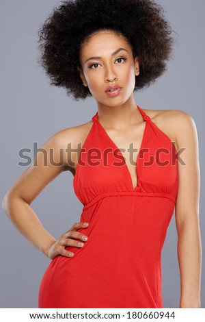 Glamorous beautiful African American woman with a shapely sexy body in a stylish red dress posing with her hand on her hip - stock photo