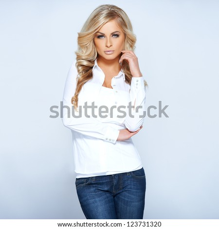 Glamorous beautiful blonde woman in a stylish white top and jeans posing standing facing the camera ,  studio portrait on white - stock photo