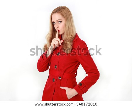 glamorous, beautiful blonde young woman with blonde hair, wearing  long, red winter trench coat.   3/4  portrait, hand in pocket, finger raised to lips with secret. isolated on white background.   - stock photo