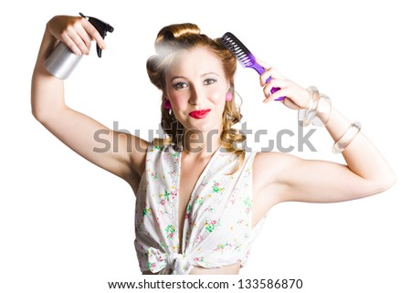 Glamorous blond woman with comb in one hand and spray in the other styling her hair on white background - stock photo