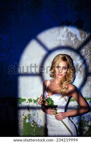 Glamorous blonde girl in a white dress with roses on the background wall, illuminated by the light - stock photo