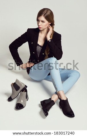 Glamorous blonde woman sitting in the studio presenting black and gray boots - stock photo