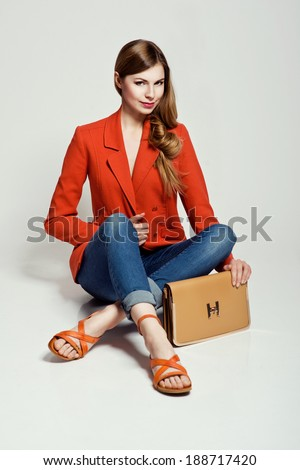 Glamorous blonde woman sitting in the studio presenting summer shoes and a handbag  - stock photo