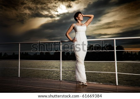 Glamorous bride. Pretty lady in a white evening dress on deck. - stock photo