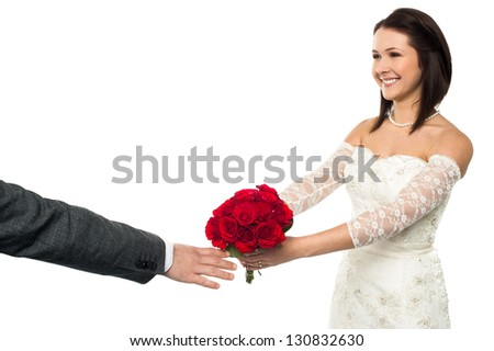 Glamorous bride with a bright smile presenting rose bouquet to the groom. - stock photo