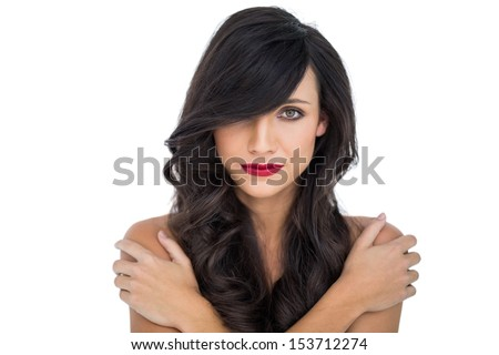 Glamorous brunette posing crossing arms on her shoulder on white background - stock photo