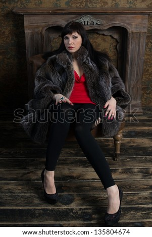 Glamorous caucasian woman sitting in a vintage interior, vertical shot - stock photo