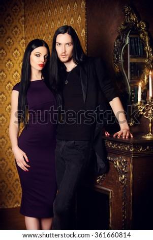 Glamorous couple in elegant evening dresses in vintage interior. Fashion shot. - stock photo