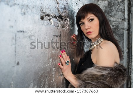 Glamorous dark-haired caucasian woman standing by the wall, wearing  fur coat and jewelry - stock photo
