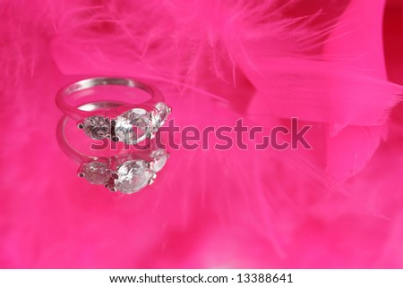glamorous diamond ring on vanity mirror with a pink feather boa in the background appropriate for invitations with copyspace
