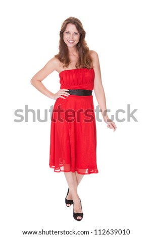 Glamorous elegant woman in a trendy red dress walking towards the camera with a lovely smile isolated on white