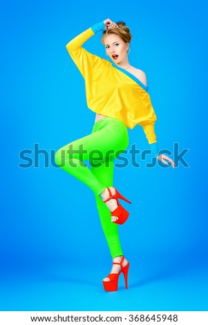 Glamorous fashion model alluring in vivid colourful clothes and high heels platform shoes. Bright fashion. Full length portrait. Studio shot. - stock photo