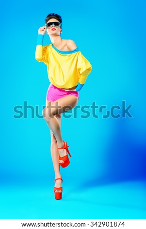 Glamorous fashion model posing in vivid colourful clothes and sunglasses. Bright fashion. Optics, eyewear. Studio shot. - stock photo