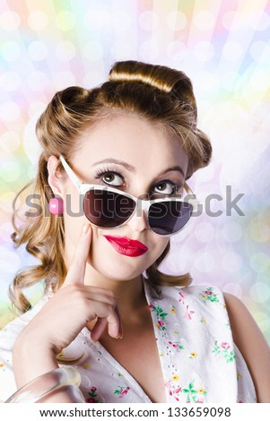 Glamorous female pinup girl thinking with hand to face on colorful disco background - stock photo