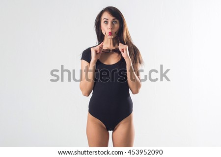 Glamorous female standing in studio, posing for portrait, wearing large sunglasses and one piece black bodysuit, holding her hands on waist, not isolated - stock photo