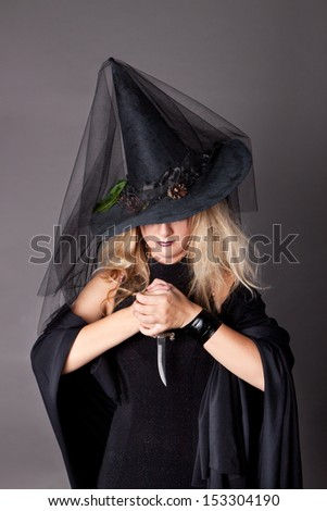 glamorous girl in black shiny dress with a dagger in his hand - the Halloween party, halloween costume, halloween witch, woman Halloween, scary halloween, spooky halloween image, vampire woman - stock photo