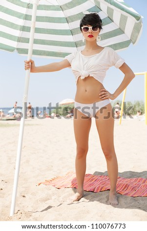 glamorous girl in retro style by color umbrella on the beach. outdoors