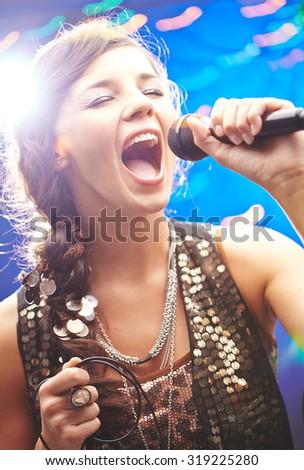 Glamorous girl singing emotional song - stock photo