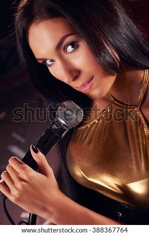 Glamorous girl singing on the stage - stock photo