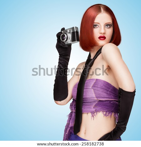 Glamorous girl, vamp style, dressed in a necktie and long gloves, taking a photo with an old vintage photo camera on blue background. - stock photo