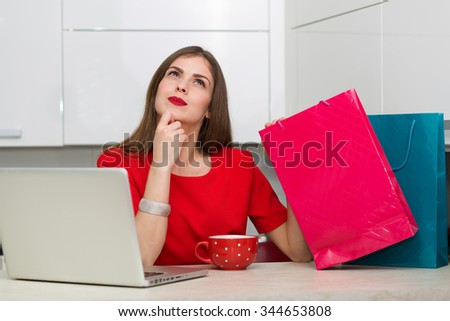 Glamorous housewife shopping online at her laptop - stock photo
