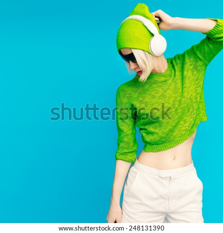 Glamorous Lada DJ in bright clothes listening to Musik on blue background - stock photo