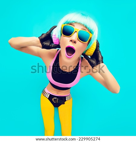 Glamorous party DJ Girl in bright clothes on a blue background listening to Music. - stock photo