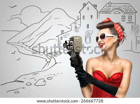 Glamorous pin-up tourist girl filming landscape with an old retro cinema 8 mm camera, standing on sketchy background. - stock photo