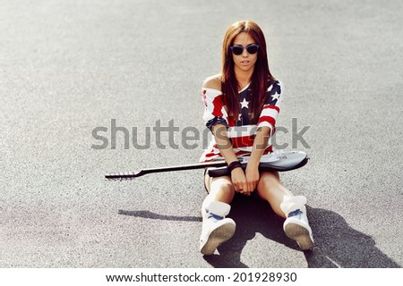 Glamorous portrait of young beautiful woman with guitar  - stock photo