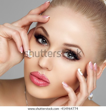 Glamorous portrait of young woman with bright makeup, fresh skin. Long eyelashes, shiny hair, highlighter, eyeshadow, blush. The beautiful girl's plump lips. The Studio. - stock photo