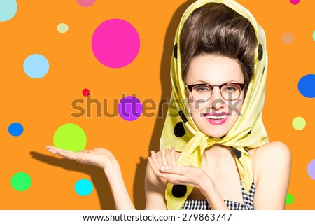 Glamorous retro lady pointing with fingers, showing against bright orange background with colorful bubbles